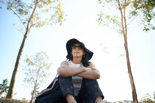 Asian woman sitting at park with sunglasses and hat