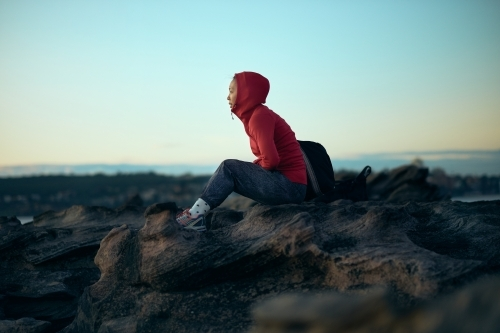 Girl looking out to ocean in winter with active wear