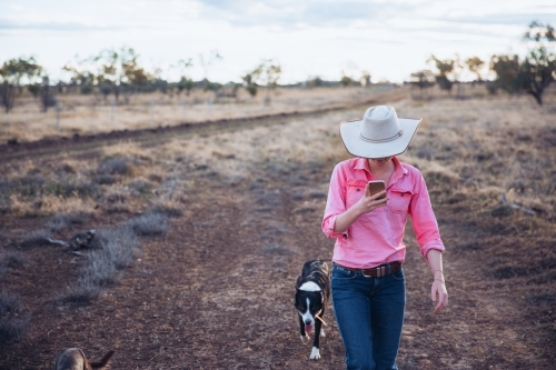 Cowgirl on smart phone with dog