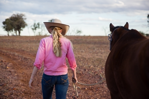 Cowgirl walking horse along dirt road