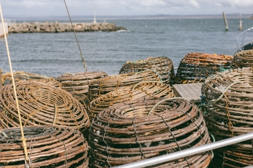Crayfish pots on a commercial fishing boat at a wharf beside ocean