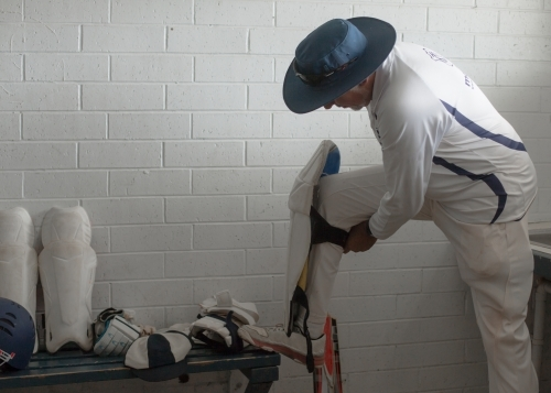 Indigenous man putting cricket pads on before batting