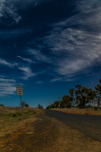 Crooked sign along a country road on a starry partly cloudy night