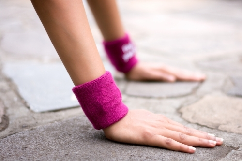 Cropped Hands Of Woman With Wristbands Exercising On Footpath