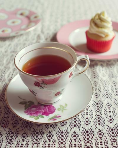 Cup of tea in vintage floral cup and saucer with cupcake behind
