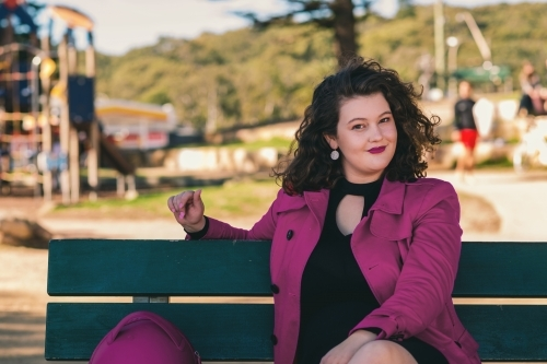 curvy woman sitting on a park bench