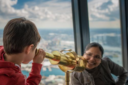 Cute 4 year old mixed race boy looks at his Asian mother with a telescope in Sydney Tower