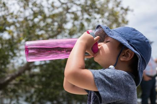 Cute mixed race boy drinks from a pink water bottle outside in the sun
