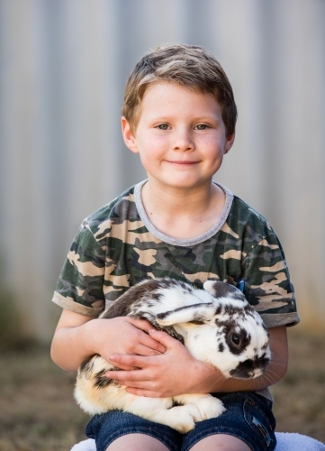Cute young boy holding pet bunny