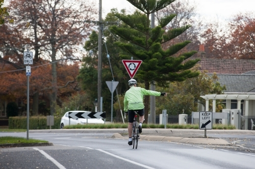 cyclist signaling as he approaches a roundabout