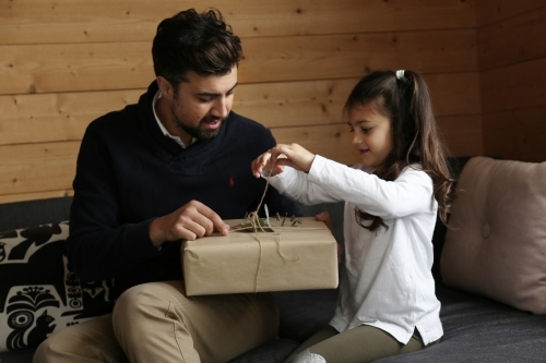 Dad and daughter opening present in lounge room