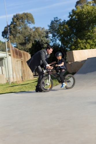 Dad in suit helping son on bike