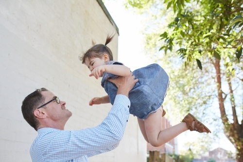 Dad playfully throwing daughter in the air