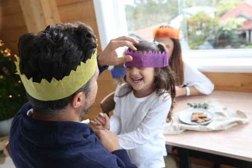 Dad with daughter laughing wearing Christmas hats