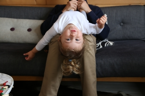 Dad with daughter upside down on couch