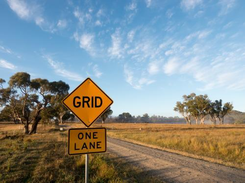 """GRID"" and ""ONE LANE"" sign on a dirt road"