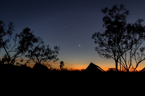 Dawn breaking over safari tents with moon and stars in dark blue sky