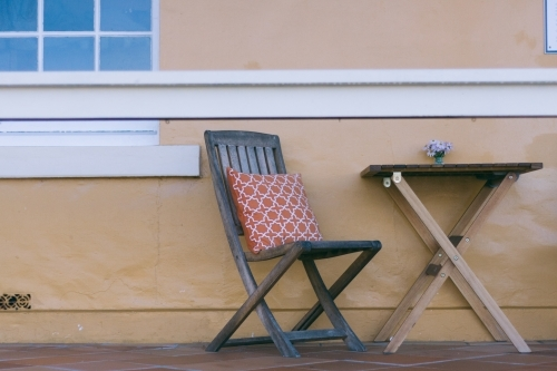 Deck chair and small table outside building