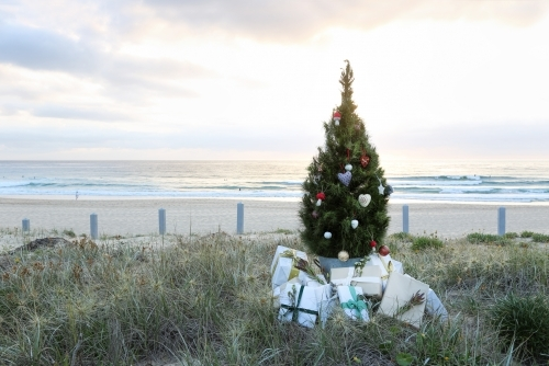Decorated Christmas tree and presents with beach sunrise in background
