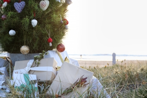 Decorated Christmas tree with presents and beach at sunrise