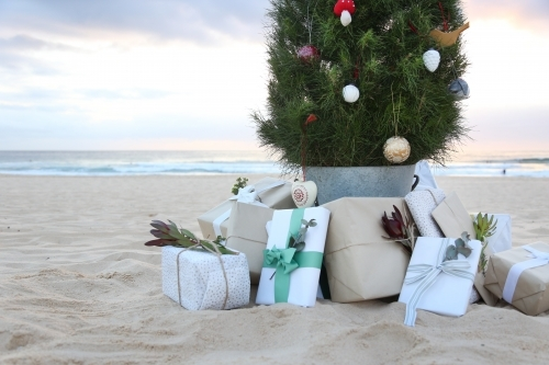 Decorated Christmas tree with presents and beach in background