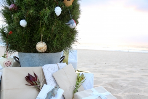 Decorated Christmas tree with presents at beach