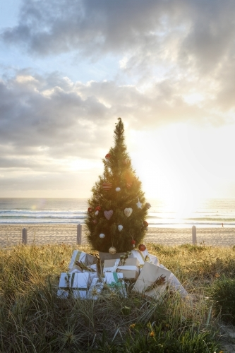 Decorated Christmas tree with presents at beach with sunrise in background