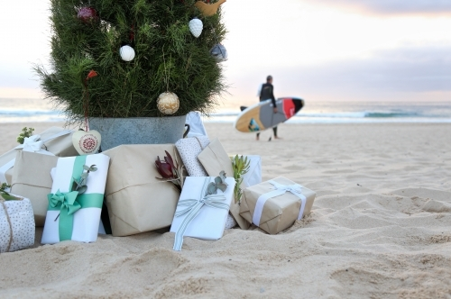 Decorated Christmas tree with presents at beach with surfer in background