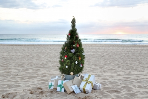 Decorated Christmas tree with presents at sunrise on beach