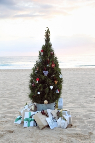 Decorated Christmas tree with presents on beach at sunrise