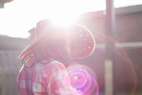 Defocused view of a young girl dressed as a cowgirl backlit by the sun (1 of 1)