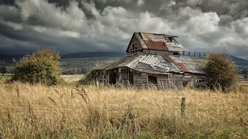 Derelict farmhouse in a paddock with dramatic sky in Tasmania