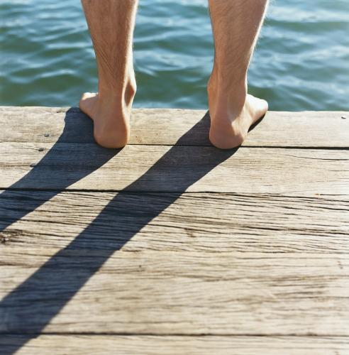 Detail of feet standing on wooden jetty with water in background