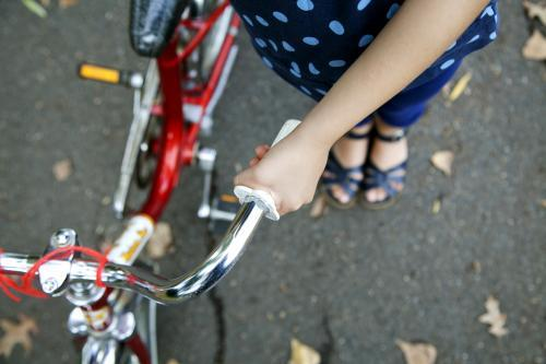 Detail of girl holding bike handle from above
