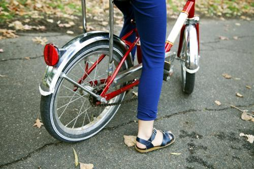Detail of girl wearing sandals riding bike