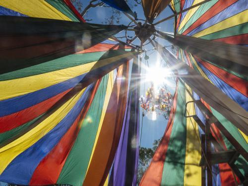 Detail of Rainbow Coloured Parachute Material at Festival with Sun