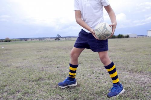 Detail of young boy passing a rugby ball in a paddock