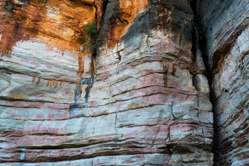 Detail shot of layered and patterned rock with orange, pink and yellow colours