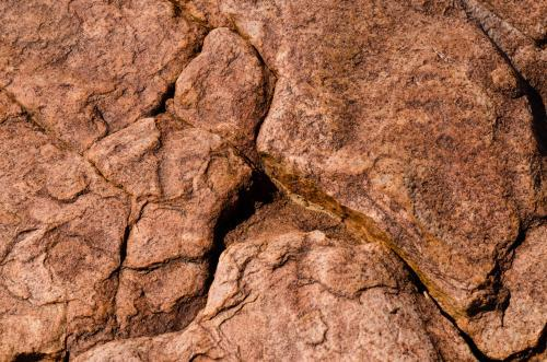 Detail shot of pink and orange rock with texture,  patterns and cracks
