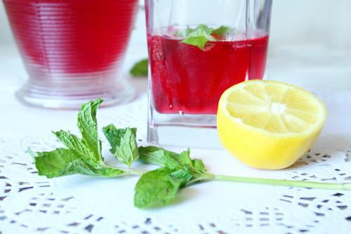 Detail view of refreshing red drink on table with lemon and mint