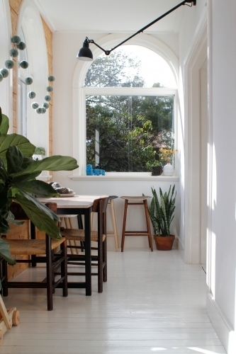 Dining table with chairs in sun room with arched windows, stools and plants