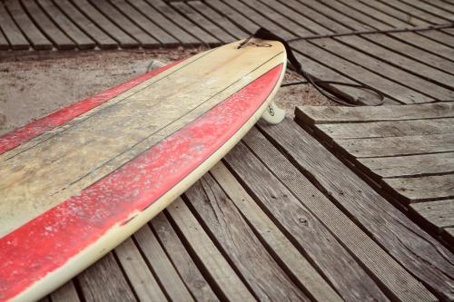Dirty surfboard on wooden planking