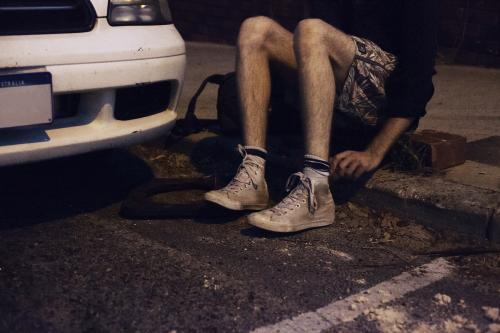 boy with dirty shoes sitting on the side walk late at night