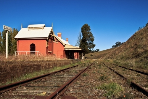 Disused country railway station with blue sky and weeds growing on tracks