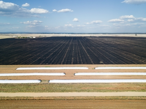 Looking down over grain storage pits and a burnt paddocks on a farm