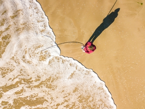 Aerial view of a fisherman and waves on a beach