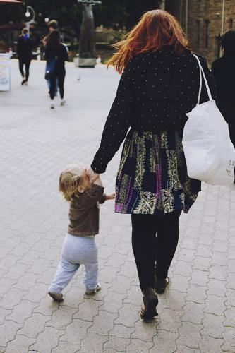 Woman walking hastily with her small child