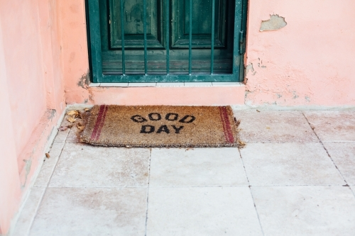 Doormat in front of green door on pink house