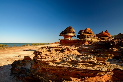 Dramatic and unusual orange rock formations on a bayside beach