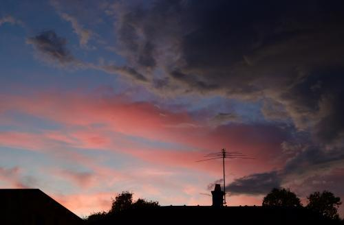 Dramatic great clouds contrasting the pink clouds of a warm sunset above a suburban skyline